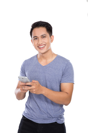 asian guy: A portrait of Asian young man holding cellphone. isolated over white