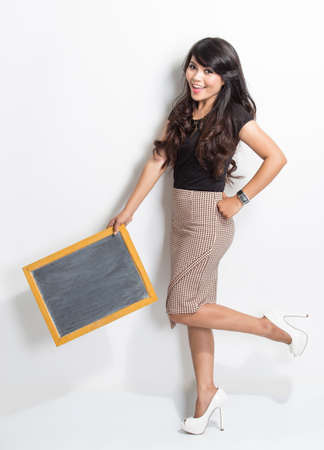 asian businesswoman: A portrait of a young woman holding a chalkboard over white background