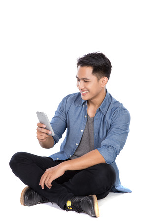 handphone: A portrait of a young asian man look at the handphone while sitting on the floor, isolated