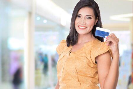 tarjeta de credito: Un retrato de una mujer asiática que soporta la tarjeta de crédito, que lo muestra a la cámara Foto de archivo