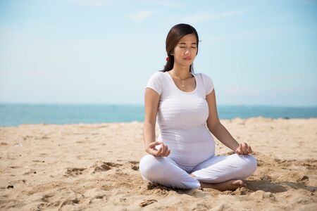 pregnancy yoga: A portrait of a pregnant asian woman doing yoga in the sea shore