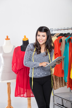 tab: A portrait of a young asian designer woman using a tablet and smiling,clothes hanged as background Stock Photo