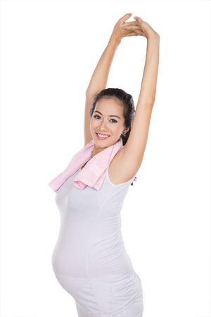 a portrait of a beautiful asian pregnant woman exersicing, isolated