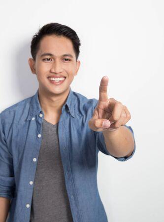 touch screen: A portrait of a young asian man pressing invincible button, hightech virtual screen
