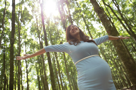 asian pregnant: A portrait of Pregnant young woman enjoying the forest with open arms Stock Photo