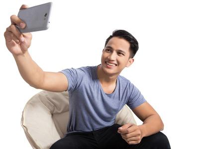 Ein Porträt einer jungen attraktiven Mann, der Fotos von ihm selbst (selfie) mit Smartphone beim Entspannen zu Hause Standard-Bild
