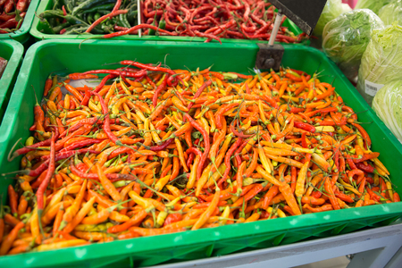 culinary tourism: A portrait of Chilli pepper on the stall in the market, asian herbs. hand trying to grab some