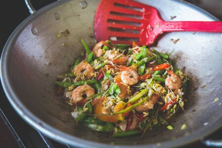 A portrait of asian cuisine, sauteing prawn, bean and vegetables