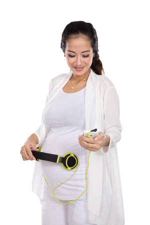 unborn: A portrait of a happy asian pregnant woman putting headphones on her belly. put some classical music on