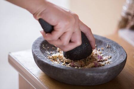 pounder: A portrait of a hand pounding herbs on a traditional pounder