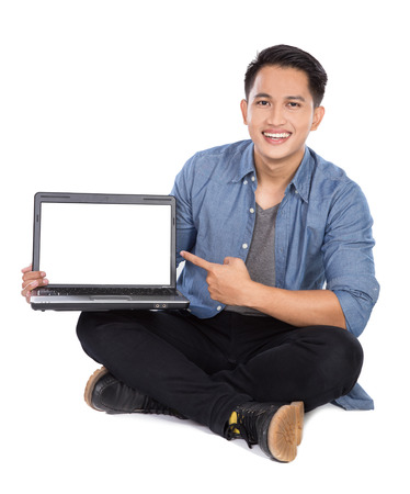 man with laptop: A portrait of young asian man presenting laptop while sitting on the floor, isolated