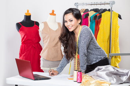 tailor shop: A portrait of a young asian designer woman using a laptop and smiling,clothes hanged as background Stock Photo
