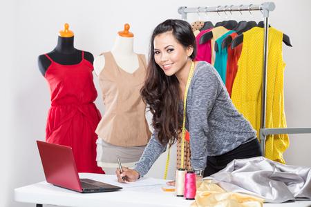 moda ropa: Un retrato de una joven diseñadora asiática con un ordenador portátil y sonriente, ropa ahorcado como fondo