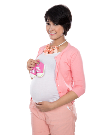 motherly: A portrait of a Pregnant asian woman holding a pair of cute pink sneakers