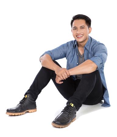 poses de modelos: Retrato de un hombre asiático joven sentado en el suelo, sonríe a la cámara Foto de archivo
