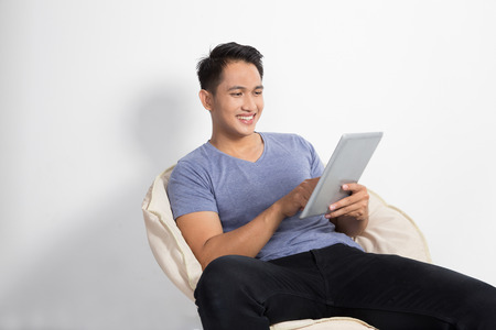 A portrait of happy young asian man holding a tablet pc while sitting on the chair, smiling Stock Photo