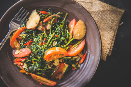 A portrait of Kale and tomato stir-fry, close up