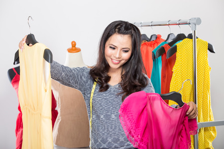 one piece dress: A portrait of a young asian designer comparing two dresses in her hands, smiling