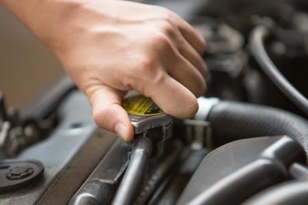 radiador: Un retrato de la tapa de presión del radiador de la mano abierta del motor del coche