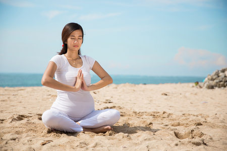 portrait of beautiful asian pregnant woman doing yoga in the beach