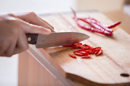 chilies: Hand slicing Chilli pepper with Knife on chopping board on wooden background. Stock Photo