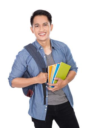 Een portret van een jonge Aziatische student met een rugzak op en houden van boeken Stockfoto