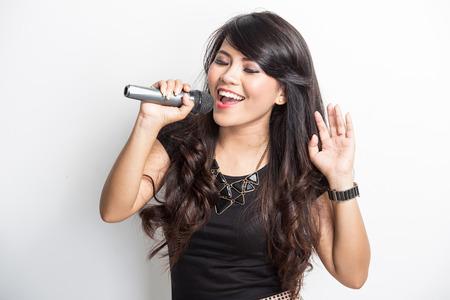 portret van mooie jonge Aziatische vrouw zingen karaoke met een microfoon