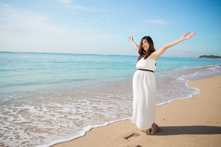vacation summer: A portrait of pretty asian pregnant woman enjoying the beach with open arms Stock Photo