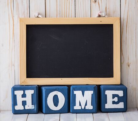 A portrait of chalkboard and HOME sign made of wooden blocks on wooden background