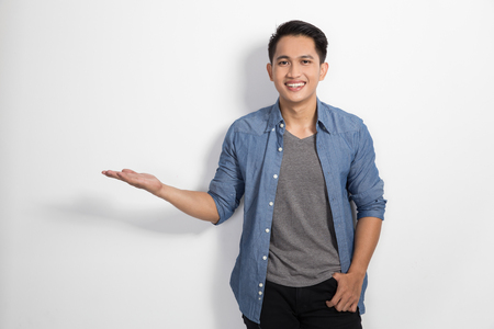 asian guy: A portrait of happy young asian man smile to the camera, prensenting hand gesture Stock Photo