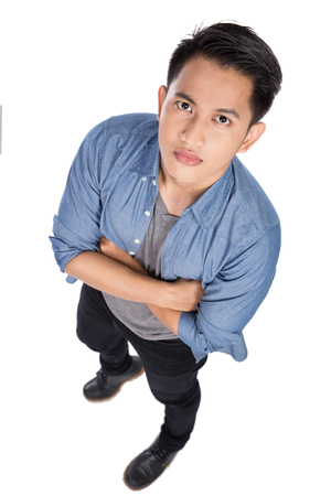 are taken: A portrait of a young asian man posing on the white background, crossed arms. Taken from above Stock Photo