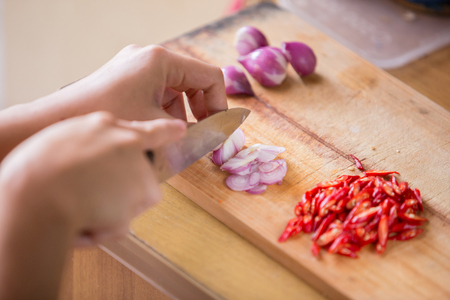 A portrait of a hands slicing onion, red onion, and chilli on wooden cutting board