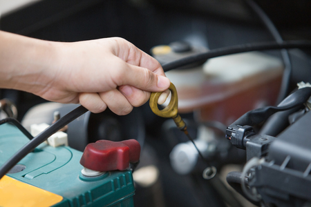 huile: Un portrait d'une main Vérification de l'huile moteur sur une voiture, une machine reliée
