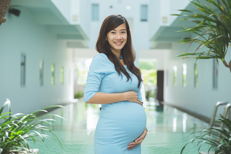 A portrait of an Asian Pregnant woman with blue dress smiling in front of a pool