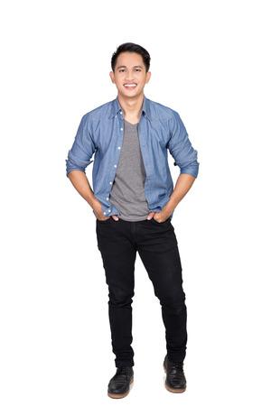 Een portret van de gelukkige jonge Aziatische man leunend op de muur poseren handen op de taille, lachen naar de camera Stockfoto