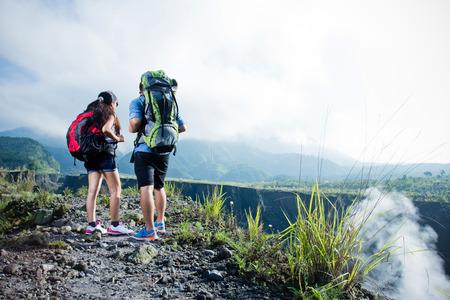 trepadoras: Un retrato del hombre y la mujer juntos en la cima de la colina después de tomar un largo viaje. la naturaleza de fondo Foto de archivo