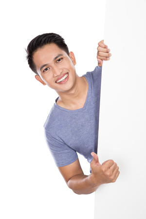 white poster: A portrait of a young asian man holding a blank banner isolated on white background. showing thumb up gesture