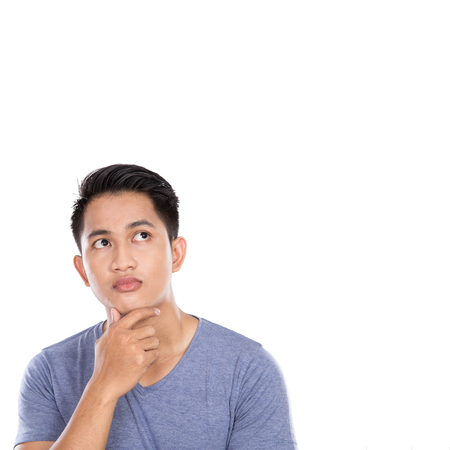 A portrait of a young asian man thinking looking up isolated over white background