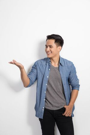 young asian: A portrait of happy young asian man smile to the camera, prensenting hand gesture Stock Photo