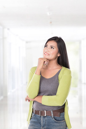 women in jeans: A portrait of a beautiful asian woman thinking, look up
