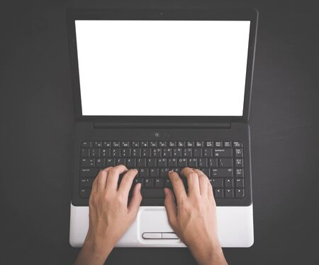 teclado: Un retrato de las manos escribiendo en el teclado del ordenador portátil en blanco en fondo negro, maqueta. pantalla vacía