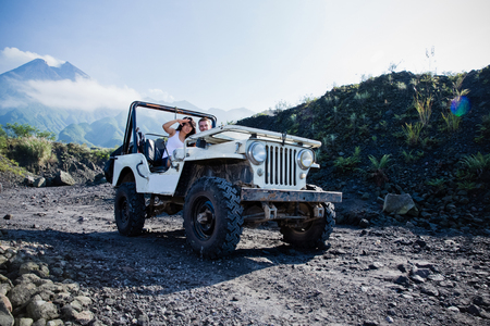 Een portret van gemengd ras paar doen wat avontuur rijdt een jeep off-road.
