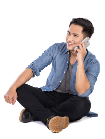 young man portrait: A portrait of a young asian man speaking on the phone while sitting on the floor, isolated