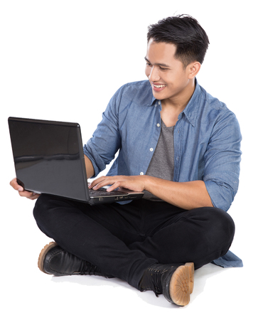 asian boy: A portrait of a young asian man using laptop while sitting on the floor, isolated in white background