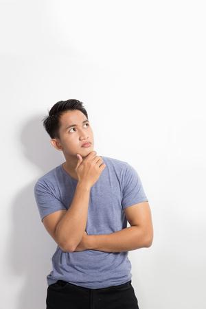 personas pensando: Un retrato de un hombre asi�tico joven que piensa mirando hacia arriba aislados sobre fondo blanco