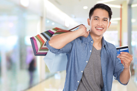 pans: A portrait of a young asian man holding shopping bags and credit card, close up
