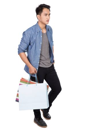 pan asian: A portrait of happy young asian man holding shopping bags, full body potrait