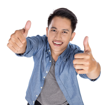 standing up: A portrait of a young asian man posing on the white background, thumbs up