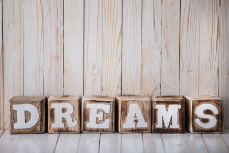A portrait of DREAMS sign made of wooden blocks on wooden background