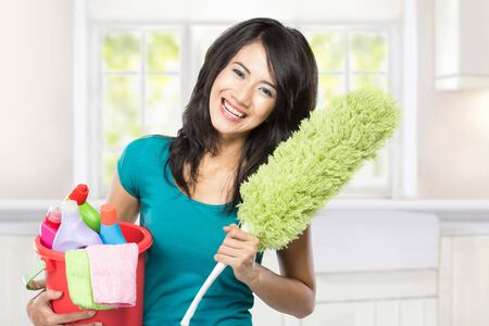 house maid: A portrait of a beautiful young asian woman holding a basket full of cleaning products ready to do a domestic chores Stock Photo